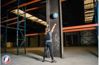 Femme portant gilet lesté noir de dos en exercice Wallball - LEVEL addict