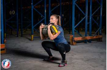 Femme en position squat avec sandbag S - LEVEL addict
