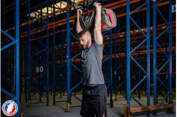 Homme en position overhead squat avec sandbag L - LEVEL addict