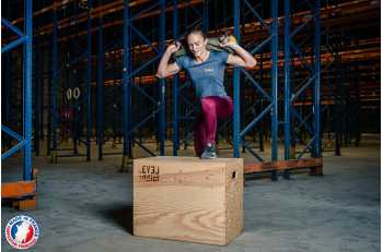 Femme en mouvement de step up avec sandbag S sur Plyo Box 3 en 1 - LEVEL addict