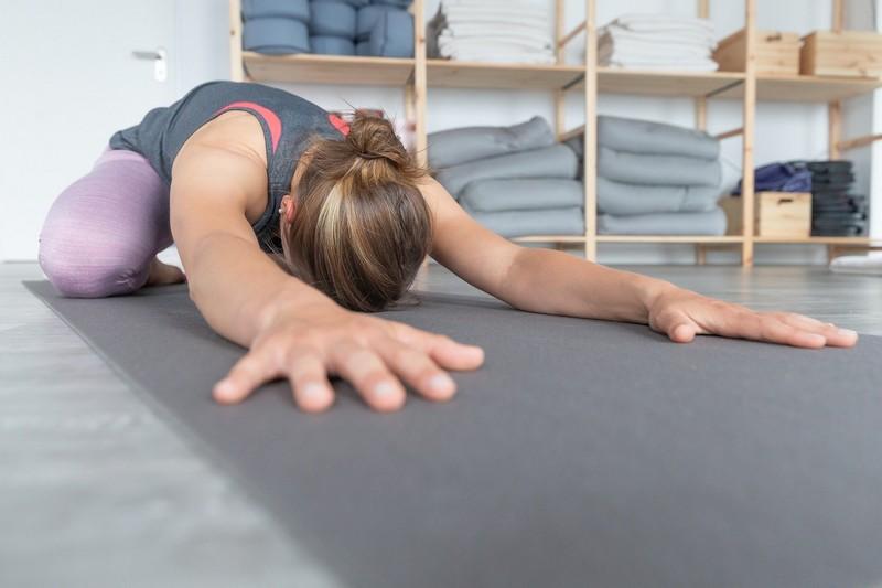 Femme pratiquant le Yoga sur un tapis de sol